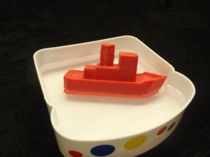 Red 3D printed toy boat floating in water