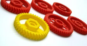6 3d printed Herringbone Gears most in red and a yellow one stands out