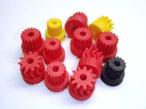 Various red, yellow and black 3d printed gears