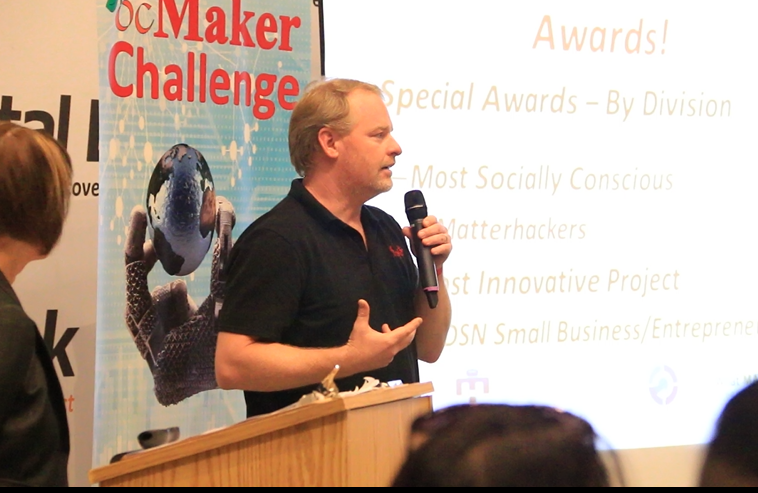 Image of Erick Wolf founder of 3D printing company Airwolf speaking to kids at a Stem Challenge event.