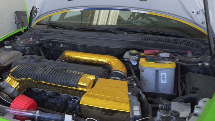 The Volvo C30's engine bay showing the 3D printed gearbox covered in gold insulation.